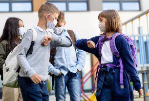 La imagen muestra dos niños regresando a clases con Tapabocas